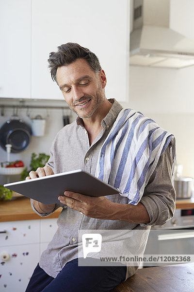 Portrait of smiling man using tablet in the kitchen