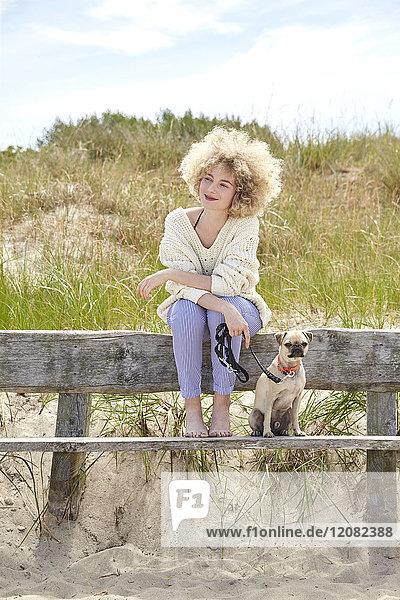 Porträt einer lächelnden jungen Frau  die mit ihrem Hund auf einer Bank in den Dünen sitzt.