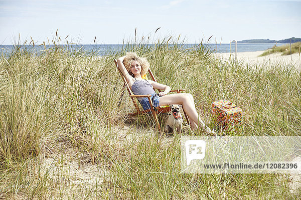 Fröhliche junge Frau sitzt auf einem Strandkorb in den Dünen.