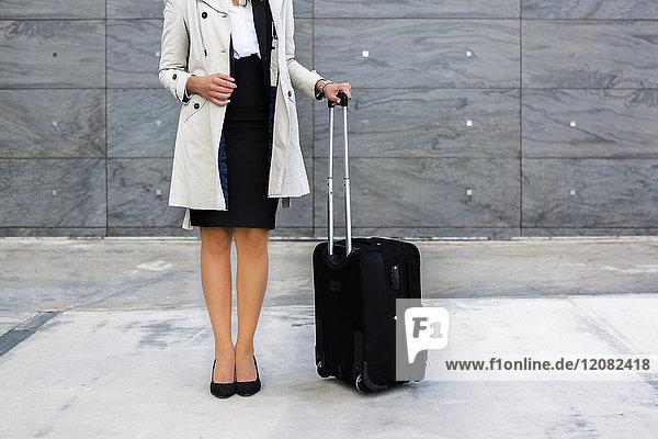 Geschäftsfrau mit Koffer in Trenchcoat  Teilansicht