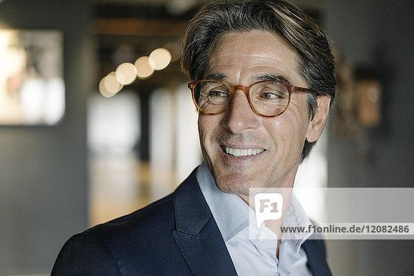Porträt eines lächelnden Geschäftsmannes mit Brille im Büro
