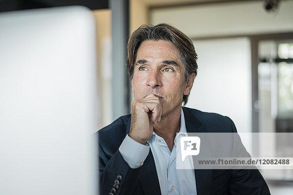 Porträt eines Geschäftsmannes im Bürodenken