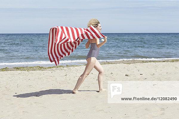 Lächelnde junge Frau mit Strandtuch vor dem Meer