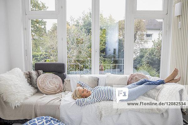 Fröhliche Seniorin entspannt auf der Couch im Wohnzimmer