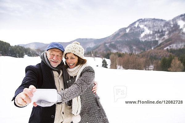 Seniorenpaar beim Küssen mit dem Handy in der Winterlandschaft
