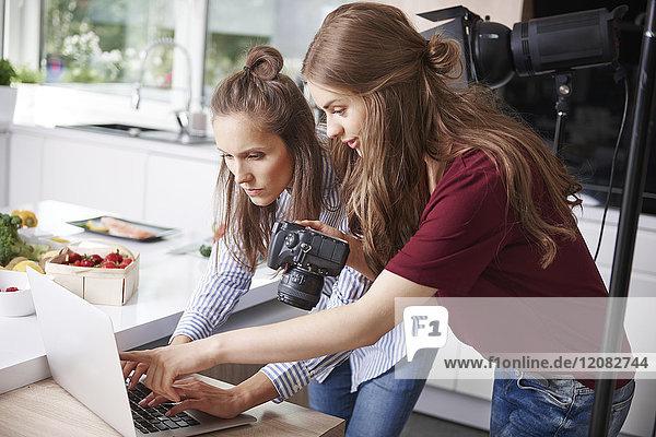 Blogger mit Laptop und Kamera in der Küche