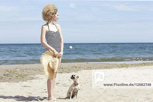 Junge Frau im Badeanzug mit Strohhut und Hund am Strand