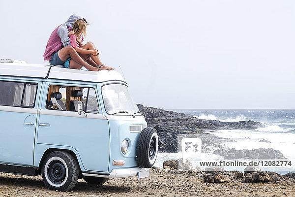 Spanien  Teneriffa  junges verliebtes Paar entspannt auf dem Autodach eines Lieferwagens
