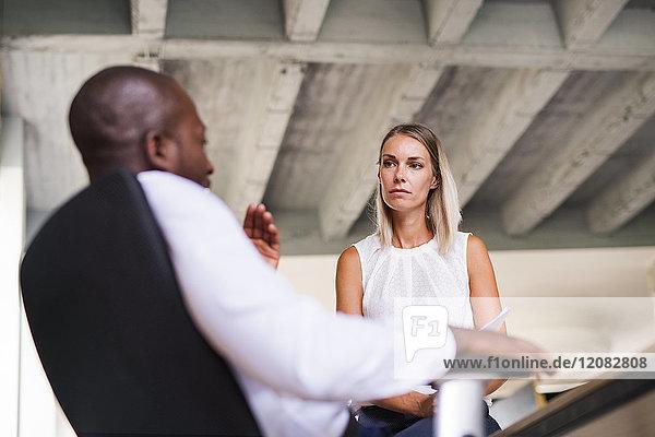 Zwei Kollegen diskutieren am Schreibtisch im Büro