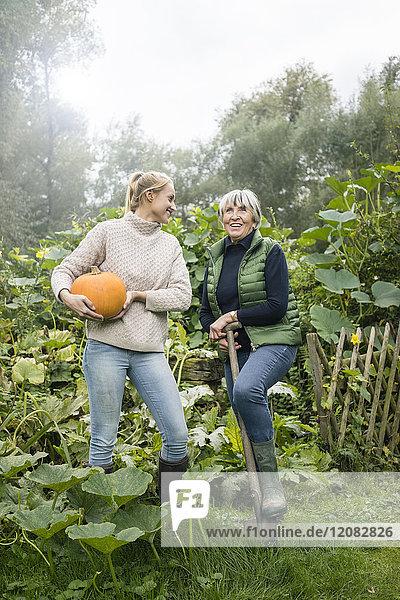 Glückliche junge Frau mit ihrer Großmutter hält Kürbis im Garten