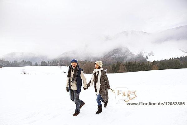 Glückliches Seniorenpaar mit Schlittenwanderung in verschneiter Landschaft
