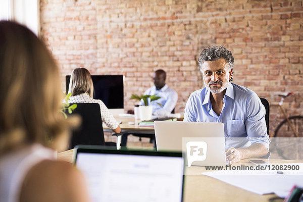 Porträt eines selbstbewussten Geschäftsmannes im Büro mit Kollegen im Hintergrund