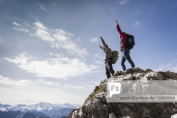 Deutschland  Bayern  Oberstdorf  zwei Wanderer  die in alpiner Landschaft auf den Felsen jubeln