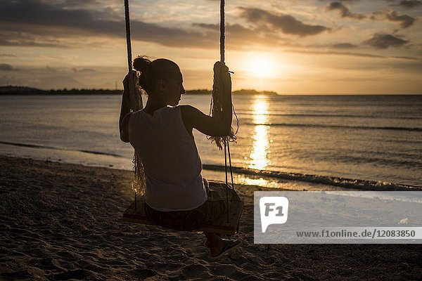 A silhouette of a young woman on a swing in a beach of Gili Air  Gili Islands  Indonesia.