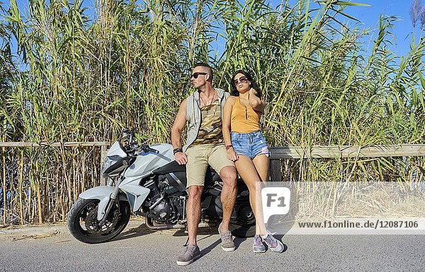 Couple leaning against motorcycle during day trip. Greek ethnicity. In holiday destination Hersonissos  Crete  Greece