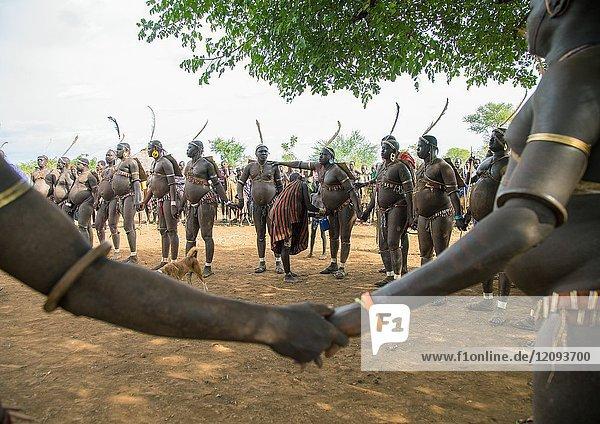 Bodi tribe fat men holding hands during Kael ceremony  Omo valley  Hana Mursi  Ethiopia.