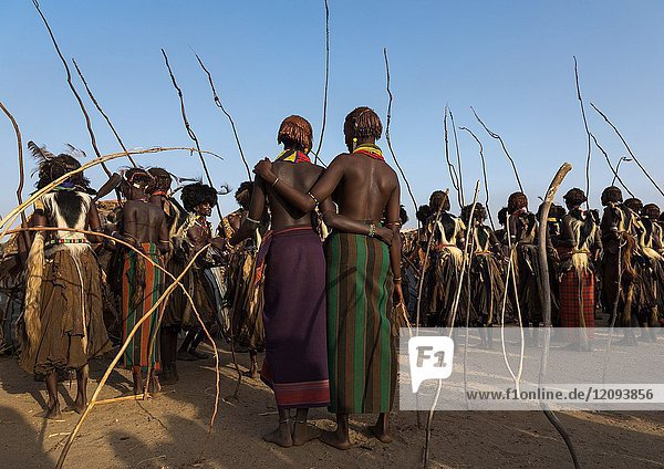 Girls looking at Dassanech men with leopard skins and ostrich feathers wigs during Dimi ceremony to celebrate circumcision of teenagers  Turkana County  Omorate  Ethiopia.
