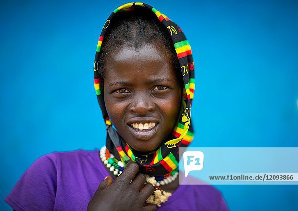 Portrait of a Bana tribe girl in front of a blue wall  Omo valley  Key Afer  Ethiopia.