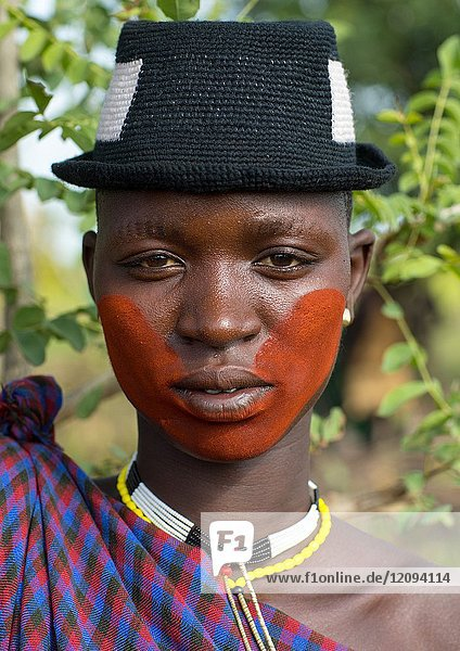 Beautiful young woman with a hat and some make up during the fat men ceremony in the Bodi tribe  Omo valley  Hana Mursi  Ethiopia.