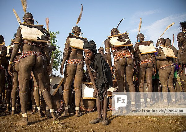 Child boy in front of Bodi tribe fat men during Kael ceremony  Omo valley  Hana Mursi  Ethiopia.