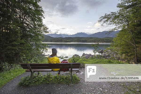 A girl reading a book on the Eibsee side. Eibsee  Garmisch Partenkirchen  Bayern  Germany.