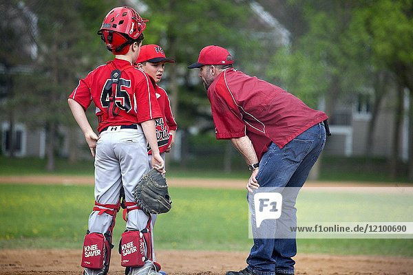 Coach  pitcher and catcher discussing the progress of the Little League baseball game at the mound. St Paul Minnesota MN USA.