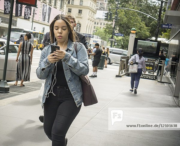 A distracted millennial  engrossed in her smartphone  walks on Sixth Avenue in New York on Friday  September 15  2017.