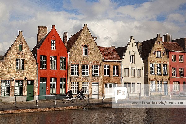 Cyclists in front of the the colorful traditional houses by the canal in the city centre  Bruges  West Flanders  Belgium  Europe.