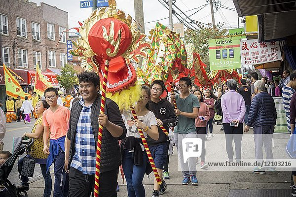Dragon dancers on Eighth Avenue in the Sunset Park neighborhood in Brooklyn in New York on Sunday  October 8  2017 after the Autumn Moon and Lantern Parade. Sunset Park has become Brooklyn's Chinatown as Chinese and other Asian groups have moved there and businesses have sprouted up to cater to them. The Lonely Planet travel guide has listed Sunset Park as one of the top ten coolest neighborhoods in the U. S. (© Richard B. Levine).