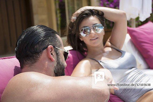 Happy couple sunbathing by the pool.