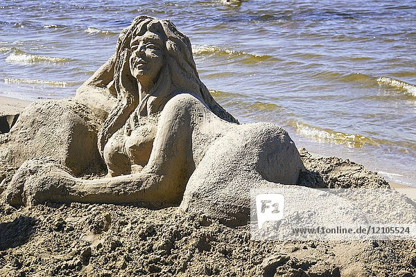 Artist makes a sand sculpture of a Mermaid. Photographed in Jurmala  Latvia.