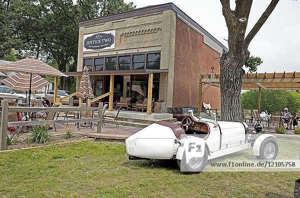 Patrons enjoying coffee and ice cream on the patios at the restored Justice Two Restaurant. Clitherall Minnesota MN USA.