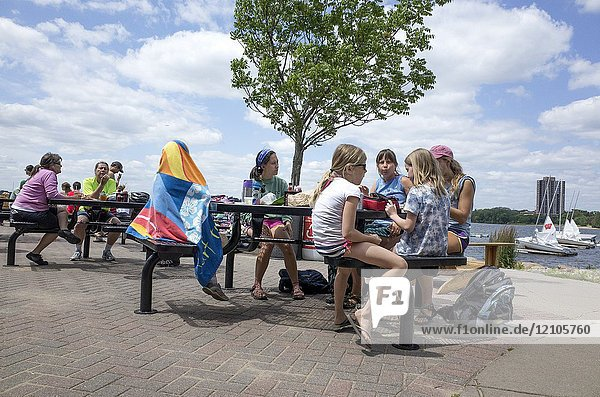 People relaxing and eating on the Lake Calhoun patio of The Tin Fish lakeside restaurant. Minneapolis Minnesota MN USA.