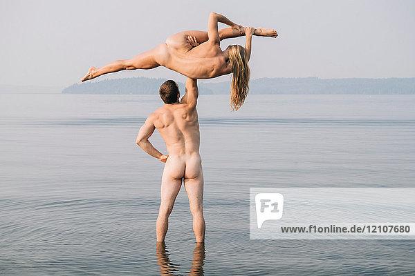 Rückansicht eines nackten Mannes  der eine nackte Frau beim Spagat hochhebt