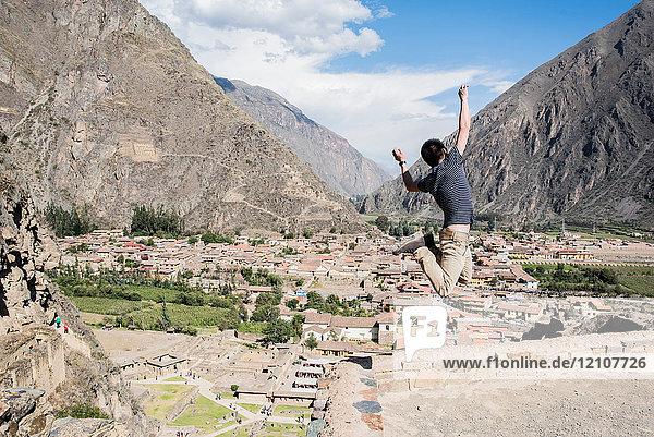 Mann springt auf die Spitze der Ollantaytambo-Ruinen  Cusco  Peru  Südamerika