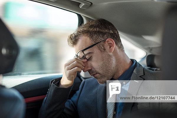 Businessman sitting in back of car  rubbing weary eyes