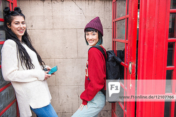 Portrait of two young stylish women leaning against red phone boxes  London  UK