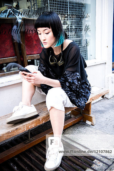 Junge stilvolle Frau wartet vor dem Geschäft und sieht sich ein Smartphone an