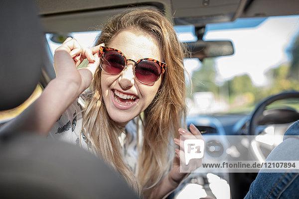 Junge Frau im Auto  über die Schulter schauend  lachend
