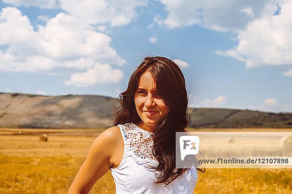 Porträt einer Frau im Weizenfeld  die lächelnd wegschaut