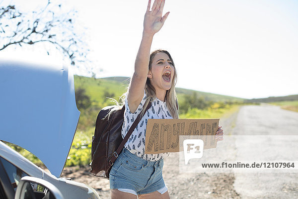 Young woman standing beside car  holding hitch-hiking sign saying 'anywhere'  gesturing with hand