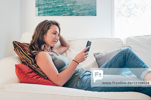 Young woman lying on sofa  looking at smartphone
