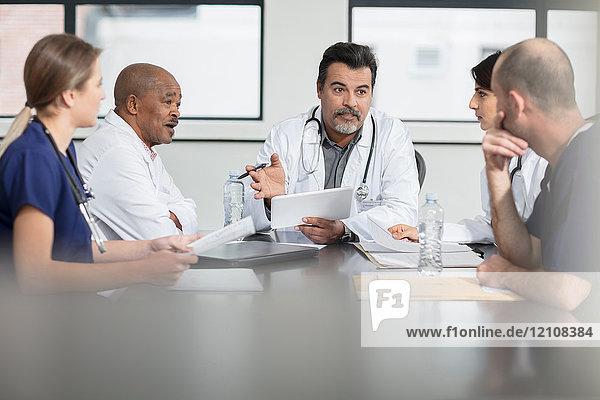 Gruppe von Ärzten  die am Tisch sitzen und diskutieren