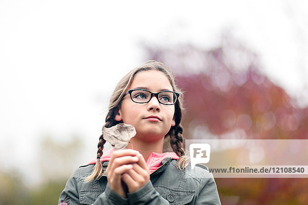 Portrait of girl with plaits and glasses holding leaf