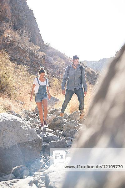 Junges Wanderpaar wandert über Felsen im Tal  Las Palmas  Kanarische Inseln  Spanien