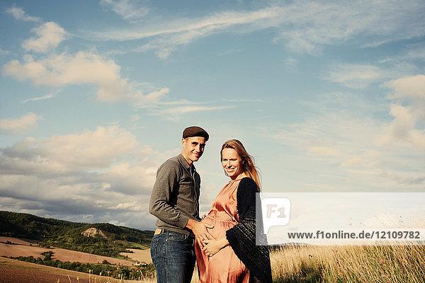 Porträt eines schwangeren Paares im mittleren Erwachsenenalter am ländlichen Hang