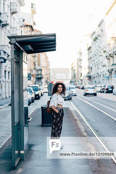 Frau steht an Bushaltestelle  Mailand  Italien