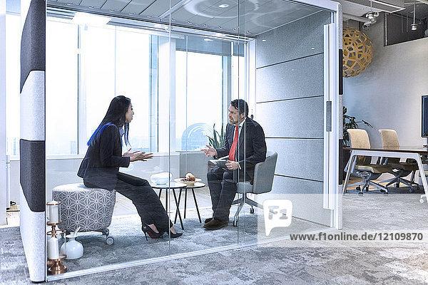 Kollegen treffen sich im Büro in einer Glaskapsel