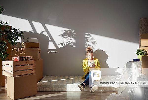 Junge Frau sitzt auf Matratze in neuem Zuhause und benutzt ein Smartphone