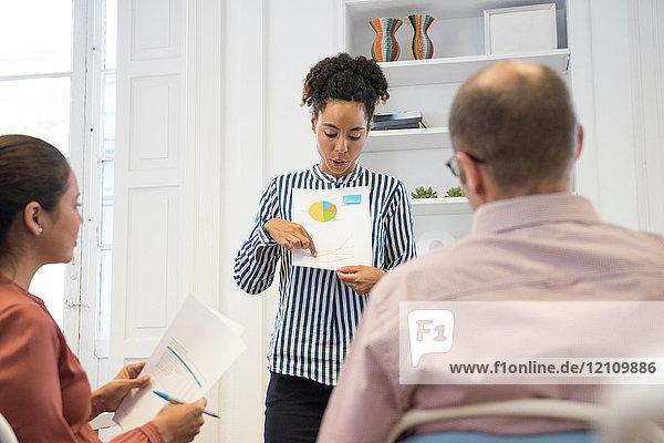 Geschäftsfrau macht Kuchendiagramm-Präsentation am Vorstandstisch